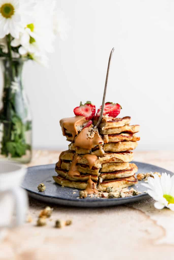 Whole30 Banana Pancakes stacked on a plate with a fork stuck into it