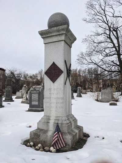 The memorial of Henry Chadwick, topped by a granite baseball and surrounded by real baseballs on the ground