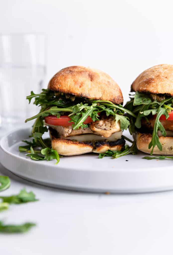 two Chicken Pesto Sandwich together on a shallow plate