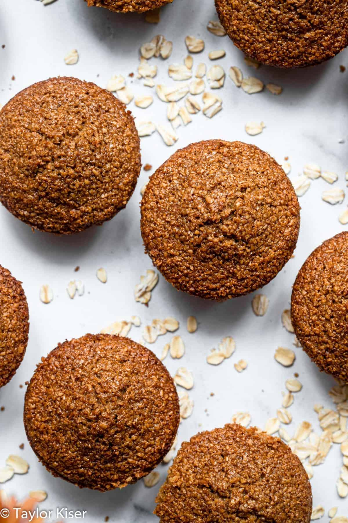 the tops of healthy oat bran muffins on a table with oats around them
