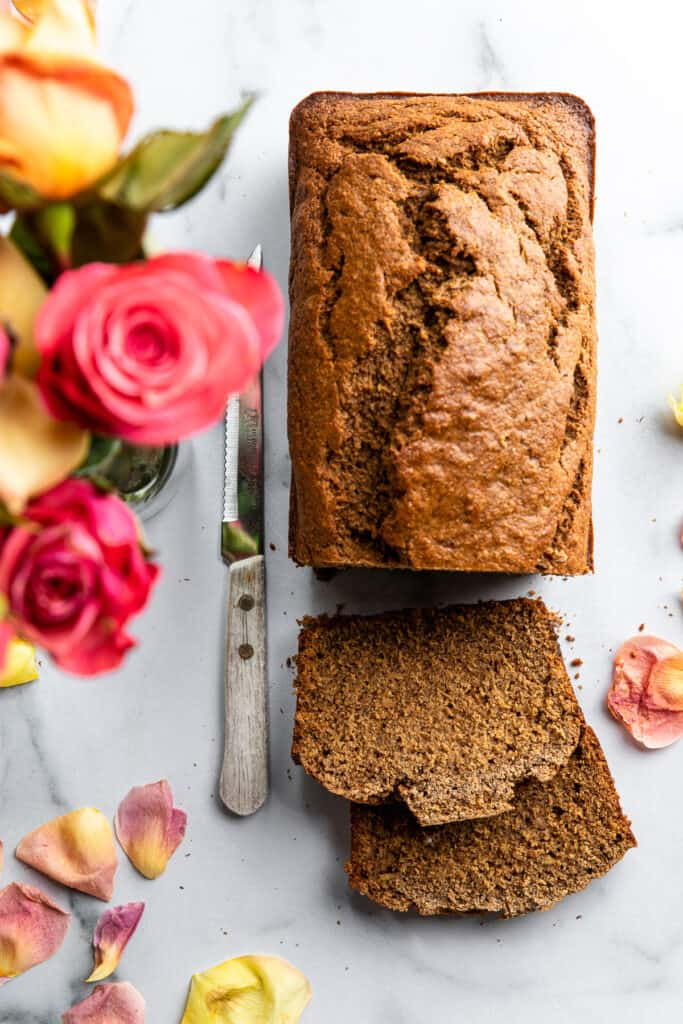 a loaf of Oat Flour Banana Bread on a table with knife
