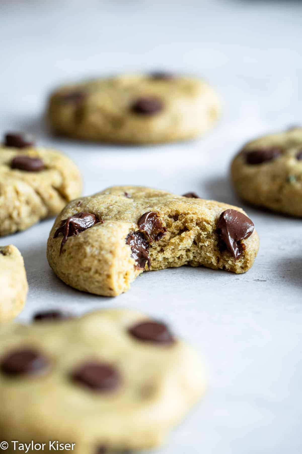 avocado chocolate chip cookies on a table with a bite taken out of it