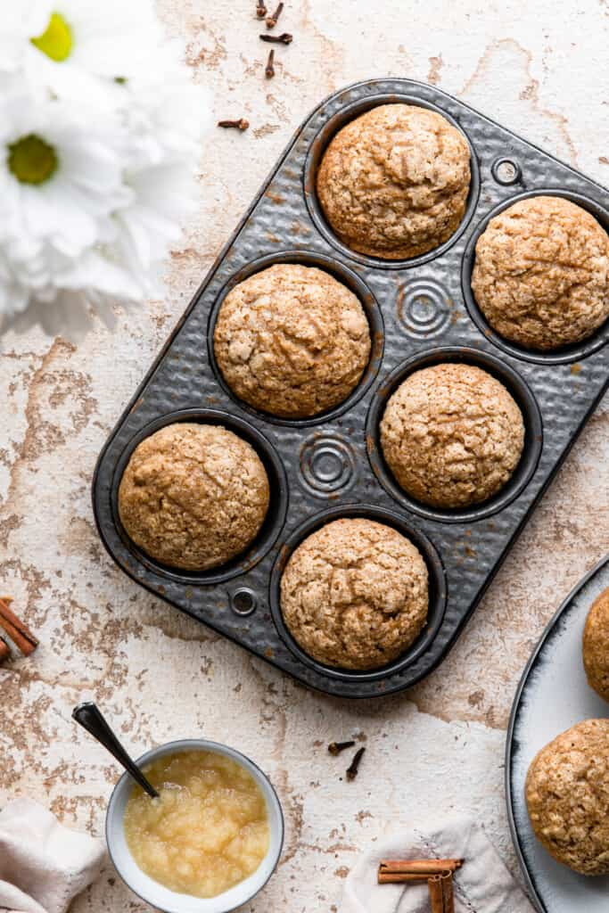 a muffin pan of Applesauce Muffins on a table
