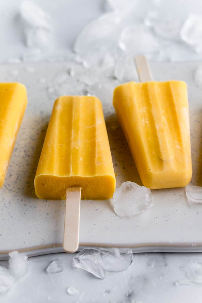 two Mango Popsicles on a board