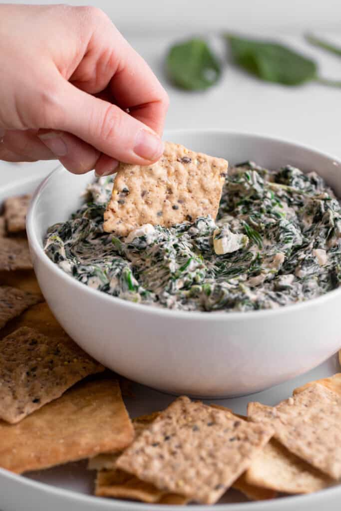a cracker being dipped into Vegan Spinach Dip