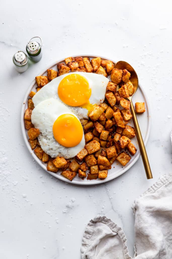 a plate full of Air Fryer Breakfast Potatoes with eggs on top