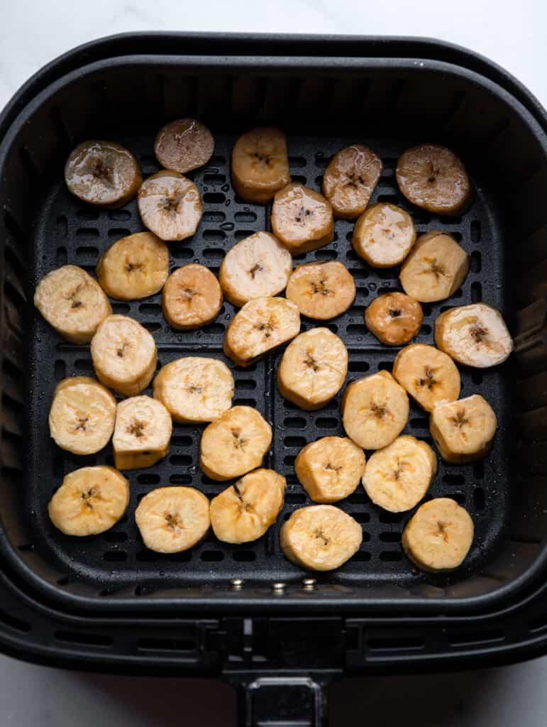 sliced Air Fryer Plantains arranged in an air fryer
