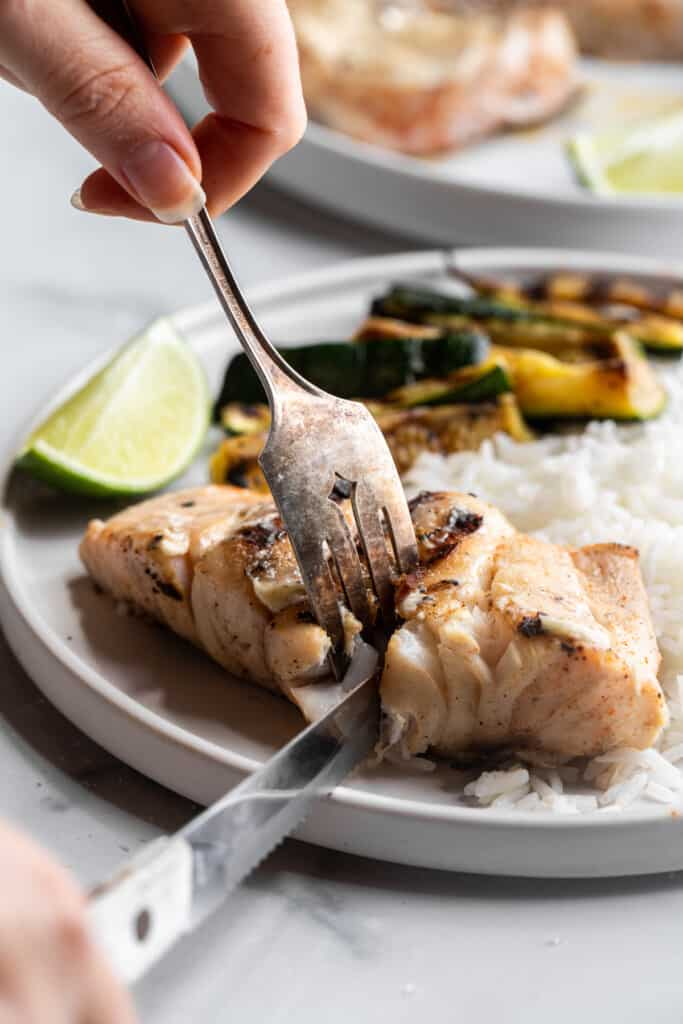 a serving of Grilled Grouper being cut up on a plate