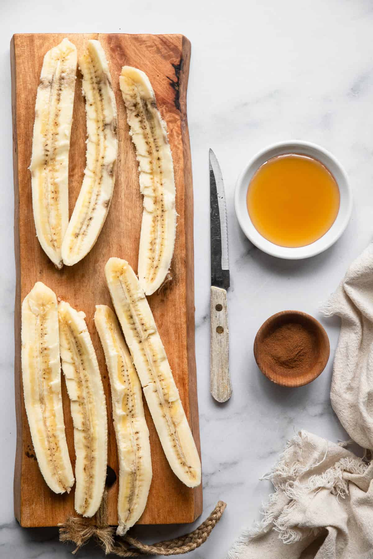 slices of banana on a cutting board with honey