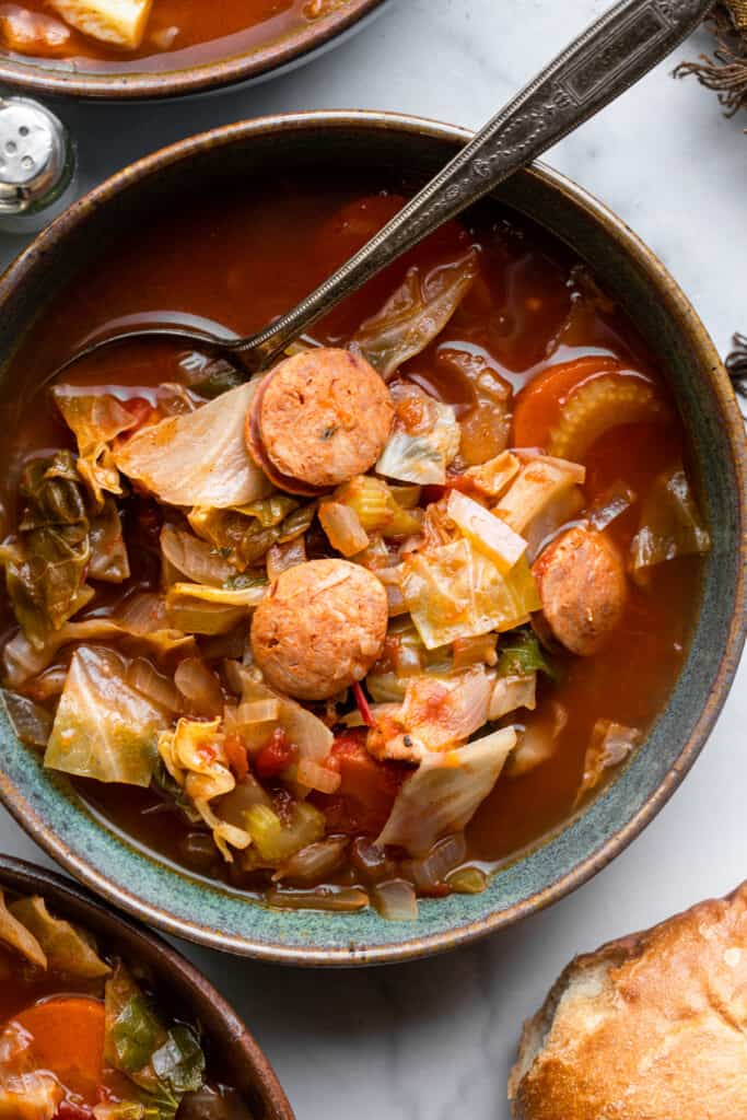 a bowl full of Cabbage Soup with Sausage with a spoon